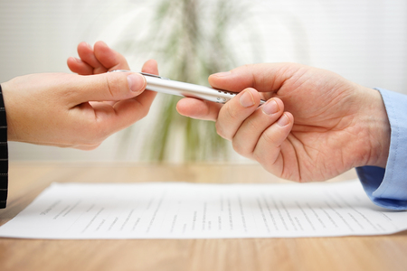 law office: Woman is taking pen from businessman to sign the document