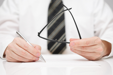 financial official: Businessman is signing agreement with glasses in hand