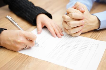 divorce: El hombre con sus manos entrelazadas está a la espera de la mujer para firmar el contrato