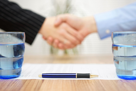 signed: signed contract with handshake in blur, focus on pen Stock Photo
