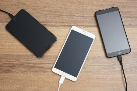 charging: Mobile smart phones  charging on wooden desk Stock Photo