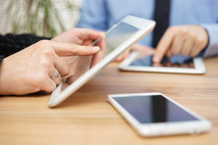 Businessman and businesswoman are using tablet computer on office desk