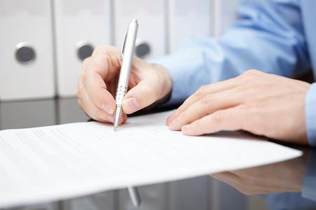 close-up van bussinessman ondertekent contract met documentatie op de achtergrond