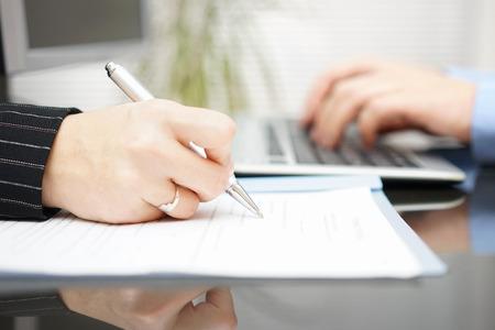 contratos: empresaria está llenando contrato y hombre de negocios está escribiendo en el ordenador en el fondo