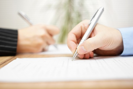 agreements: man and woman writing on document