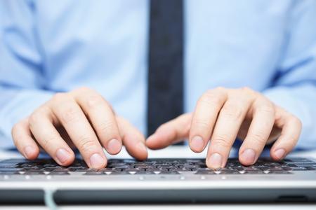 Geschäftsmann im blauen Hemd auf Computertastatur Standard-Bild