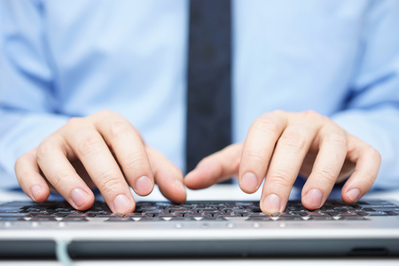 Businessman in blue shirt typing on computer keyboard Banque d'images