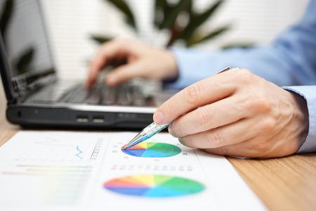 Close-up van zakenman handen bedrijfs rapport bekijken en te typen op een laptop computer