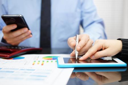 auditoría: Mujer y hombre de negocios con el teléfono móvil en la mano de examinar el informe en el ordenador tableta