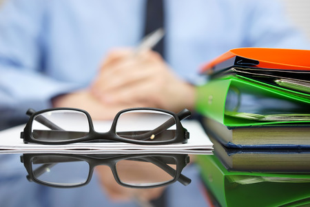 paper document: Businessman is reading or thinking in front of contract and documentation with glasses in focus Stock Photo