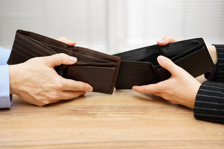 male hand: man and woman shows empty wallet to each other