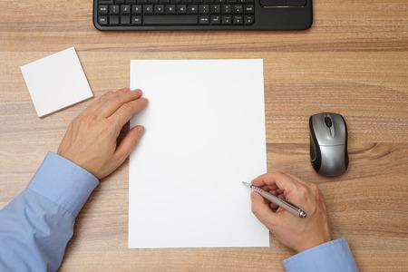 empezar: Hombre de negocios con papel en blanco y un bolígrafo en la mano para comenzar con la escritura. vista superior