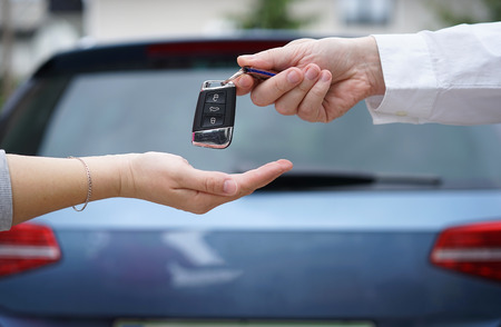 car dealer gives the customer the car keys with car in backgorund