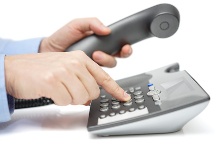telephone: Businessman is dialing telephone number with handset in hand Stock Photo