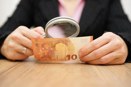 dinero falso: Empresaria mirando a través de un dinero lupa. concepto de fraude