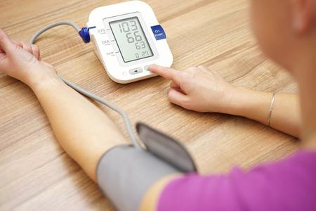 hipertension: La mujer está tomando el cuidado de la salud con el monitor de ritmo hogar y la presión arterial Foto de archivo