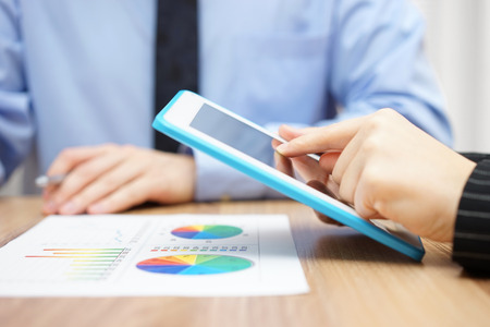 sales report: businessman and businesswoman working together on project with tablet and paper report