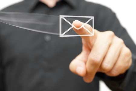 email us: Businessman pressing flying virtual email icon Stock Photo
