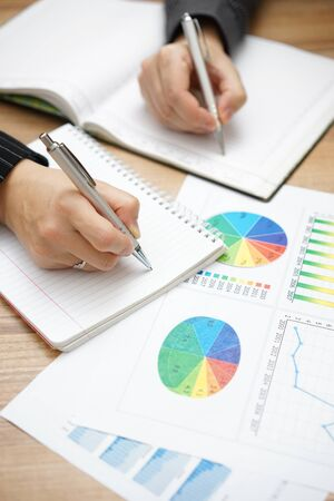make summary: Hands of business people  writing down tasks to do after brainstorming Stock Photo