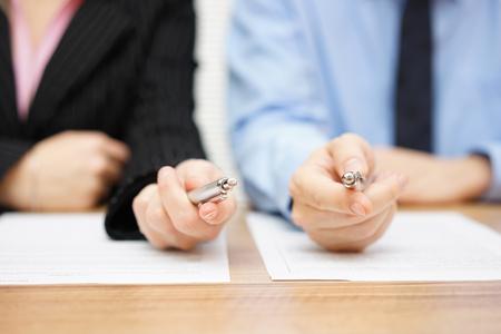 entrevista de trabajo: Dos agentes que dan a su cliente una pluma para firmar un acuerdo Foto de archivo