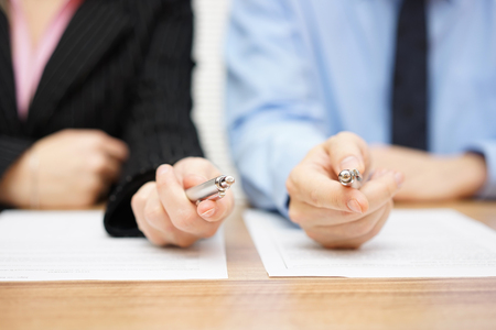 hands at work: Two agents giving his client a pen to sign a deal