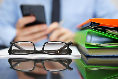 to phone calls: businessman is calling financial adviser for help.Focus on glasses Stock Photo