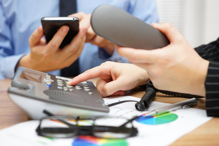 Occupied business people in office are dialing on land line telephone and and using mobile smart phone