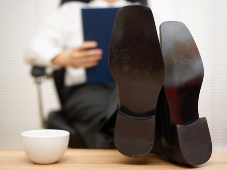 businessman sitting on chair reading report with his feet on the table, focus on shoes