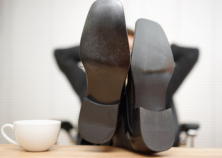 feet on desk: Relaxed businessman is sitting in office with feet on the desk