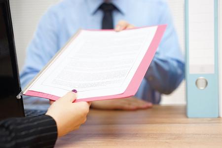 contrato de trabajo: mujer de negocios está pasando documento al director Foto de archivo
