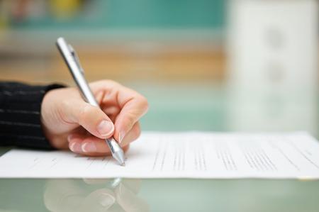 papier a lettre: femme remplit le document sur la table de verre, la profondeur de champ