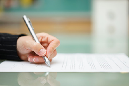 pen and paper: woman is filling document on glass table, shallow depth of field