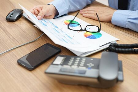 financial audit: busy businessman analyzing a lot of  graphs and business data at  the desk