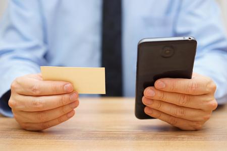empresario utilizar la información de contacto de la tarjeta de visita para ponerse en contacto con su cliente