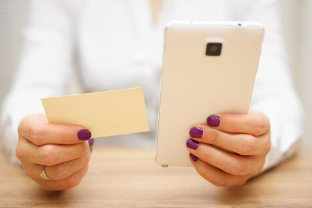 mobile telephone: woman reading telephone number from business card and calling customer on smart mobile phone Stock Photo