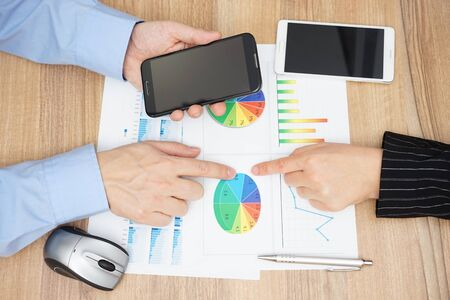 conclusion: vista desde arriba de la gente de negocios análisis de informe de ventas y la lectura de la información en el teléfono móvil Foto de archivo
