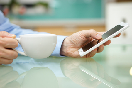 man is using smart mobile phone and drinking coffee at home