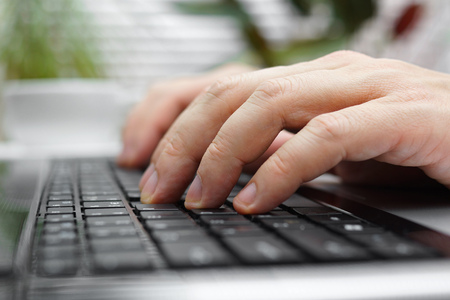 join: closeup of male fingers on laptop keyboard