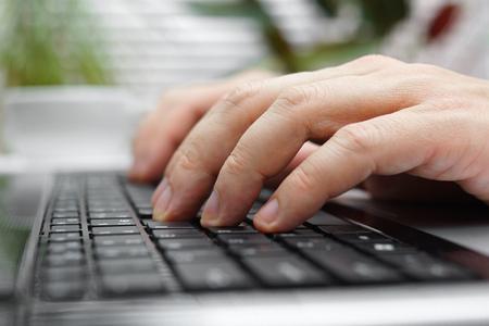 usando computadora: primer plano de los dedos en el teclado del ordenador portátil masculinas