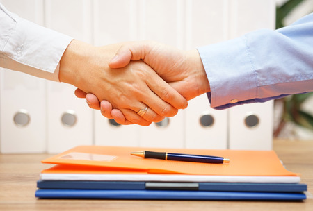 firm: business man and woman are handshaking over documents in with office in background Stock Photo
