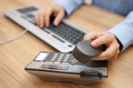 businessman hand picking up telephone receiver on business workplace 스톡 콘텐츠