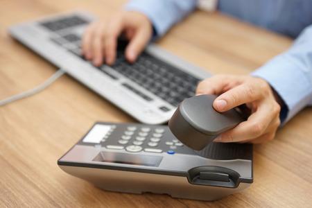 empresas: empresario de la mano recogiendo tel�fono del receptor en el lugar de trabajo de negocios