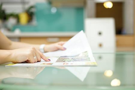 persona leyendo: mujer está leyendo la revista en la cocina Foto de archivo