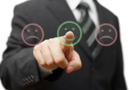 smile icon: Business man choose  smile icon  and not the sad one Stock Photo