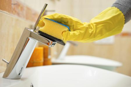 handen in handschoenen met spons schoonmaken pijp en kraan Stockfoto