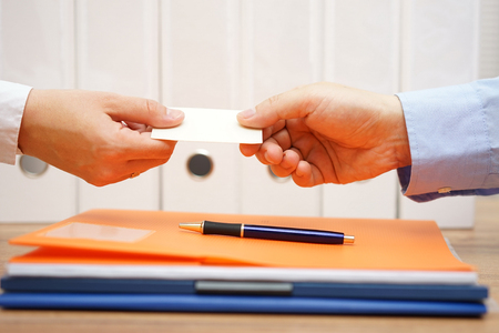 man holding card: business partners are exchanging business cards over documents after meeting Stock Photo