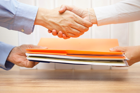 office documents: entrepreneur shaking hands with his accuntant after passing documenation and invoices Stock Photo