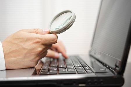 Zakenman is met behulp van vergrootglas op computer laptop. Internet search en beveiligingsconcept Stockfoto - 47707883