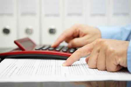 impuestos: hombre de negocios está leyendo el documento financiero y el cálculo de resultado Foto de archivo