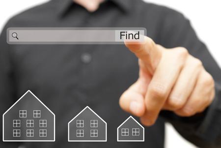 Geschäftsmann ist mit Internet-Suchleiste auf Immobilien finden